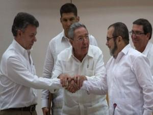 El presidente de Colombia, Juan Manuel Santos, y el líder de la guerrilla de las FARC, Rodrigo Londoño (alias Timochenko) sellan el pacto con un apretón de manos con el presidente cubano Raul Castro Como Testigo.