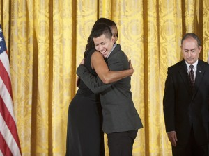 Jefry Amaya, beneficiario del proyecto OYE, se abraza con la primera dama Michelle Obama.