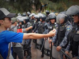 Los policias ofrecen palos golpes y gas lacrimogeno mientras los estudiantes los reciben con flores