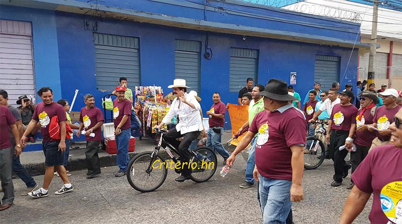 Mel Zelaya llega en bicicleta a la marcha de los trabajadores